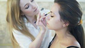 Η κινηματογράφηση σε πρώτο πλάνο ενός όμορφου νέου brunette ήρθε στον καλλιτέχνη makeup της να κάνει μια σύνθεση ημέρας Ένας ειδι φιλμ μικρού μήκους