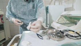 Η κινηματογράφηση σε πρώτο πλάνο, εργασία χειρούργων στο νοσοκομείο απολυμαίνει τα ιατρικά όργανα πριν από τη λειτουργία Γιατρός  απόθεμα βίντεο