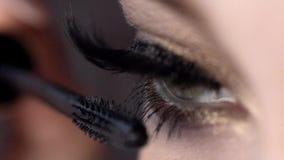 Η κινηματογράφηση σε πρώτο πλάνο εφαρμόζει mascara στα eyelashes του όμορφου θηλυκού ματιού r Απίστευτο μήκος μαστιγίων με την έξ φιλμ μικρού μήκους