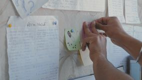 Η κινηματογράφηση σε πρώτο πλάνο, ινδικά χέρια σπουδαστών συνδέεται με την αυτοκόλλητη ετικέττα τοίχων φιλμ μικρού μήκους