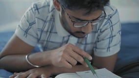 Η κινηματογράφηση σε πρώτο πλάνο, ινδικός σπουδαστής στα γυαλιά διαβάζει σκεπτικά τις καταχωρήσεις στο λαϊκό ψέμα στο κρεβάτι απόθεμα βίντεο