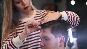 Η κινηματογράφηση σε πρώτο πλάνο, κύριος κομμωτής hairstyle και ύφος με το ψαλίδι και τη χτένα Έννοια Barbershop φιλμ μικρού μήκους