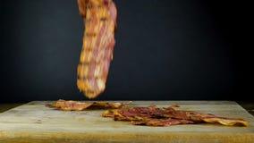 Η κινηματογράφηση σε πρώτο πλάνο μιας φέτας του μπέϊκον τηγάνισε σε καυτά τηγανητά μπέϊκον σε ένα τηγάνι απόθεμα βίντεο