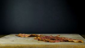 Η κινηματογράφηση σε πρώτο πλάνο μιας φέτας του μπέϊκον τηγάνισε σε καυτά τηγανητά μπέϊκον σε ένα τηγάνι φιλμ μικρού μήκους