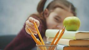 Η κινηματογράφηση σε πρώτο πλάνο μιας όμορφης μαθήτριας κάθεται στον πίνακα σε ένα γκρίζο υπόβαθρο Κατά τη διάρκεια αυτού παίρνει απόθεμα βίντεο