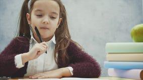 Η κινηματογράφηση σε πρώτο πλάνο μιας όμορφης μαθήτριας κάθεται στον πίνακα σε ένα γκρίζο υπόβαθρο Κατά τη διάρκεια αυτής της περ φιλμ μικρού μήκους