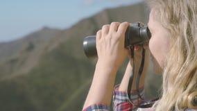 Η κινηματογράφηση σε πρώτο πλάνο μια χαριτωμένη ξανθή γυναίκα με τις διόπτρες πάνω από ένα βουνό απολαμβάνει μια περιβάλλουσα ομο απόθεμα βίντεο