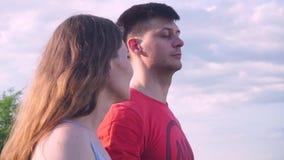 Η κινηματογράφηση σε πρώτο πλάνο, ο όμορφοι τύπος και το κορίτσι εξετάζουν προς τα εμπρός, η μια την άλλη, αγκάλιασμα, χαμόγελο απόθεμα βίντεο