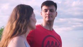 Η κινηματογράφηση σε πρώτο πλάνο, ο όμορφοι τύπος και το κορίτσι εξετάζουν προς τα εμπρός, η μια την άλλη, αγκάλιασμα, χαμόγελο φιλμ μικρού μήκους