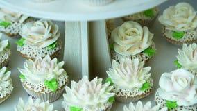 Η κινηματογράφηση σε πρώτο πλάνο, ποικίλα εύγευστα επιδόρπια, cupcakes, κέικ κρέμας, κτυπημένη κρέμα, λουλούδια έκανε με την κρέμ φιλμ μικρού μήκους