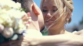Η κινηματογράφηση σε πρώτο πλάνο, πορτρέτο, η νύφη αγκαλιάζει το νεόνυμφο το χέρι με μια ανθοδέσμη βρίσκεται στον ώμο του νεόνυμφ απόθεμα βίντεο