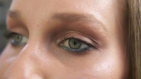 Η κινηματογράφηση σε πρώτο πλάνο που πυροβολείται μιας γυναίκας που ανοίγει τα πράσινα μάτια της με την ελαφριά ημέρα ετοιμάζει κ φιλμ μικρού μήκους