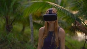 Η κινηματογράφηση σε πρώτο πλάνο που πυροβολείται μιας όμορφης νέας γυναίκας χρησιμοποιεί μια κάσκα VR σε ένα τροπικό πάρκο Ένα π φιλμ μικρού μήκους