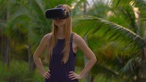 Η κινηματογράφηση σε πρώτο πλάνο που πυροβολείται μιας όμορφης νέας γυναίκας χρησιμοποιεί μια κάσκα VR σε ένα τροπικό πάρκο Ένα π απόθεμα βίντεο