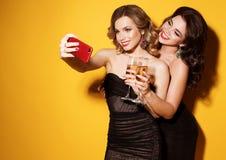Η κινηματογράφηση σε πρώτο πλάνο που πυροβολείται της ομάδας γελώντας κοριτσιών που έχουν το κόμμα, παίρνει selfie με το smartpho Στοκ Φωτογραφίες
