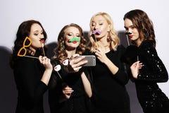 Η κινηματογράφηση σε πρώτο πλάνο που πυροβολείται της ομάδας γελώντας κοριτσιών που έχουν το κόμμα, παίρνει selfie με το smartpho Στοκ Εικόνες