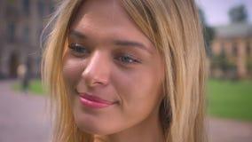 Η κινηματογράφηση σε πρώτο πλάνο που χαμογελά το χαριτωμένο κοίταγμα κοριτσιών κατά μέρος και το κεκλεισμένων των θυρών, μόνιμο ε απόθεμα βίντεο