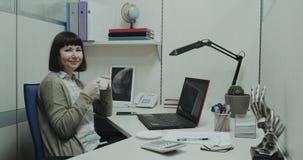 Η κινηματογράφηση σε πρώτο πλάνο στη μικρή νέα γυναίκα γωνιών γραφείων παίρνει ένα σπάσιμο στον καφέ κατανάλωσης γραφείων της και απόθεμα βίντεο
