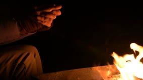 Η κινηματογράφηση σε πρώτο πλάνο στο πλήρες σκοτάδι μια γυναίκα θερμαίνει τα χέρια του ανοίγει πυρ Φοίνικες γυναικών από την πυρκ απόθεμα βίντεο