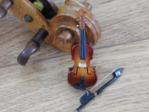 Η κινηματογράφηση σε πρώτο πλάνο της μικρογραφίας ενός βιολιού με το τόξο επάνω σε ένα βιολί φυσικού μεγέθους στοκ φωτογραφίες