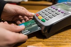 Η κινηματογράφηση σε πρώτο πλάνο της πληρωμής με πιστωτική κάρτα της American Express, αγοράζει και πωλεί τις δημόσιες σχέσεις στοκ εικόνες