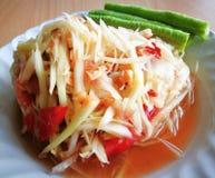 Η κινηματογράφηση σε πρώτο πλάνο της πράσινης papaya σαλάτας ή το SOM Tum ` ` σε Ταϊλανδό με cowpea στο άσπρο πιάτο βάζει στον ξύ Στοκ Εικόνες