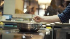 Η κινηματογράφηση σε πρώτο πλάνο του αρχιμάγειρα παραδίδει ένα μπλε ελεγμένο πουκάμισο προετοιμάζοντας κάποιο πιάτο σε μια κουζίν απόθεμα βίντεο