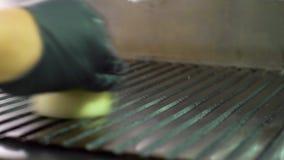 Η κινηματογράφηση σε πρώτο πλάνο του αρχιμάγειρα παραδίδει το γάντι λιπαίνοντας τη μεγάλη επαγγελματική σόμπα σχαρών με το κρεμμύ φιλμ μικρού μήκους