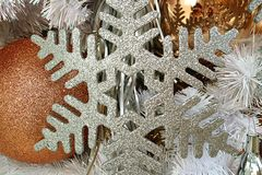 Η κινηματογράφηση σε πρώτο πλάνο του ασημιού ακτινοβολεί διαμορφωμένη snowflake διακόσμηση Χριστουγέννων με τη χρυσή διαμορφωμένη Στοκ φωτογραφίες με δικαίωμα ελεύθερης χρήσης
