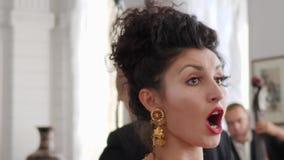 Η κινηματογράφηση σε πρώτο πλάνο του ελκυστικού κοριτσιού με τα κόκκινα χείλια στα όμορφα σκουλαρίκια τραγουδά συναισθηματικά φιλμ μικρού μήκους