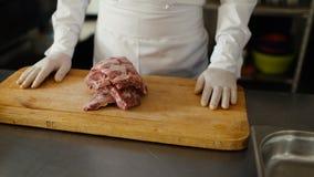 Η κινηματογράφηση σε πρώτο πλάνο του επαγγελματικού αρχιμάγειρα προετοιμάζει τα πλευρά κρέατος στον τέμνοντα πίνακα στην κουζίνα  Στοκ εικόνες με δικαίωμα ελεύθερης χρήσης