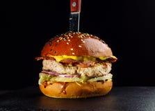 Η κινηματογράφηση σε πρώτο πλάνο του εύγευστου φρέσκου σπιτιού έκανε burger με το μαρούλι, το τυρί, το κρεμμύδι και την ντομάτα Στοκ Εικόνα