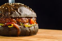 Η κινηματογράφηση σε πρώτο πλάνο του εύγευστου φρέσκου σπιτιού έκανε burger βόειου κρέατος με το μαρούλι, το τυρί, το κρεμμύδι κα Στοκ Φωτογραφία