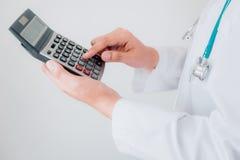 Η κινηματογράφηση σε πρώτο πλάνο του θηλυκού γιατρού υπολογίζει το κόστος ότι ιατρικής στο νοσοκομείο γραφείων, θηλυκός ιατρικός  στοκ εικόνες