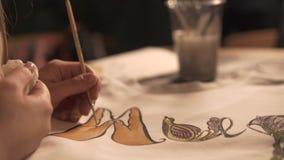 Η κινηματογράφηση σε πρώτο πλάνο του θηλυκού χεριού με το πινέλο χρωματίζει το άσπρο πουκάμισο σε ένα εργαστήριο φιλμ μικρού μήκους