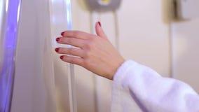 Η κινηματογράφηση σε πρώτο πλάνο του κοριτσιού σε μια άσπρη τήβεννο ανοίγει την πόρτα του σολαρήου στο σαλόνι SPA φιλμ μικρού μήκους