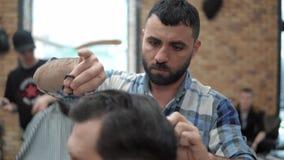 Η κινηματογράφηση σε πρώτο πλάνο του κουρέα κόβει την τρίχα από το ψαλίδι στο barbershop Χέρια κομμωτών ` s στη διαδικασία εργασί φιλμ μικρού μήκους