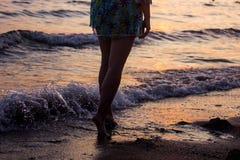 Η κινηματογράφηση σε πρώτο πλάνο το των γυμνών ποδιών ατόμων ` s που περπατούν σε μια παραλία στο ηλιοβασίλεμα, με μια άκρη κυμάτ Στοκ Φωτογραφίες