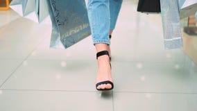 Η κινηματογράφηση σε πρώτο πλάνο των θηλυκών ποδιών στα μοντέρνα μαύρα παπούτσια με τις αγορές τοποθετεί το περπάτημα στη λεωφόρο απόθεμα βίντεο