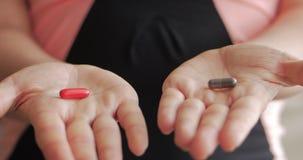 Η κινηματογράφηση σε πρώτο πλάνο των θηλυκών χεριών, κάποιος χύνει μια δέσμη των οπιούχων χαπιών συνταγών στο χέρι Έννοια της υγε απόθεμα βίντεο