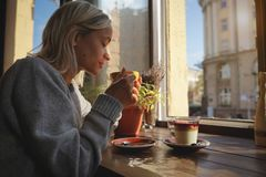 Η κινηματογράφηση σε πρώτο πλάνο των χεριών γυναικών ` s με ένα κέικ φλιτζανιών του καφέ, οι ακτίνες ήλιων ` s λάμπει μέσω ενός π στοκ εικόνες