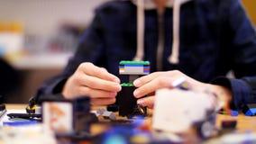 Η κινηματογράφηση σε πρώτο πλάνο, χέρια παιδιών ` s κρατά ένα πολύχρωμο μικρό ρομπότ, μηχανή, που συγκεντρώνεται από έναν σχεδιασ απόθεμα βίντεο
