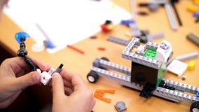 Η κινηματογράφηση σε πρώτο πλάνο, χέρια παιδιών ` s κρατά ένα πολύχρωμο μικρό ρομπότ, μηχανή, που συγκεντρώνεται από έναν σχεδιασ φιλμ μικρού μήκους