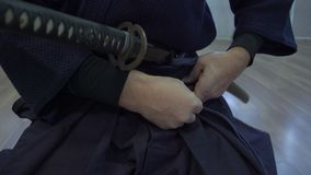 Η κινηματογράφηση σε πρώτο πλάνο, χέρια της συνεδρίασης Σαμουράι στο πάτωμα και την πιέτα στο catan ` s ξίφος ζωνών στη θήκη, το  απόθεμα βίντεο