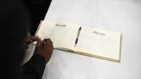 Η κινηματογράφηση σε πρώτο πλάνο, χέρι γράφει τα συγχαρητήρια στο βιβλίο των συγχαρητηρίων στο γάμο φιλμ μικρού μήκους