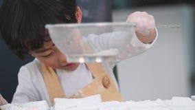 Η κινηματογράφηση σε πρώτο πλάνο χαριτωμένη λίγου ασιατικού αγοριού που κοσκινίζει το αλεύρι ζύμης με sifter το τρυπητό κόσκινων  απόθεμα βίντεο