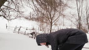 Η κινηματογράφηση σε πρώτο πλάνο, χαρούμενο κορίτσι στην κουκούλα ρίχνει τις χιονιές στο δάσος απόθεμα βίντεο
