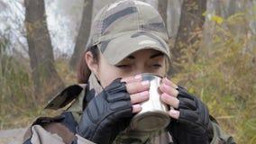 Η κινηματογράφηση σε πρώτο πλάνο, όμορφη γυναίκα στη στρατιωτική κάλυψη πίνει το καυτό τσάι κουπών μετάλλων στο ομιχλώδες πρωί απόθεμα βίντεο
