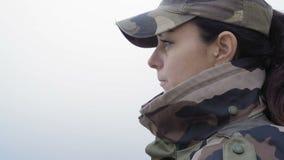 Η κινηματογράφηση σε πρώτο πλάνο, όμορφη γυναίκα στη στρατιωτική κάλυψη πίνει το καυτό τσάι από την κούπα μετάλλων στο υπόβαθρο π απόθεμα βίντεο