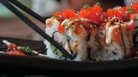 Η κινηματογράφηση σε πρώτο πλάνο chopsticks κρατά ότι τα σούσια κυλούν ένα πιάτο στο εστιατόριο ιαπωνικός παραδοσιακός κουζίνας φιλμ μικρού μήκους